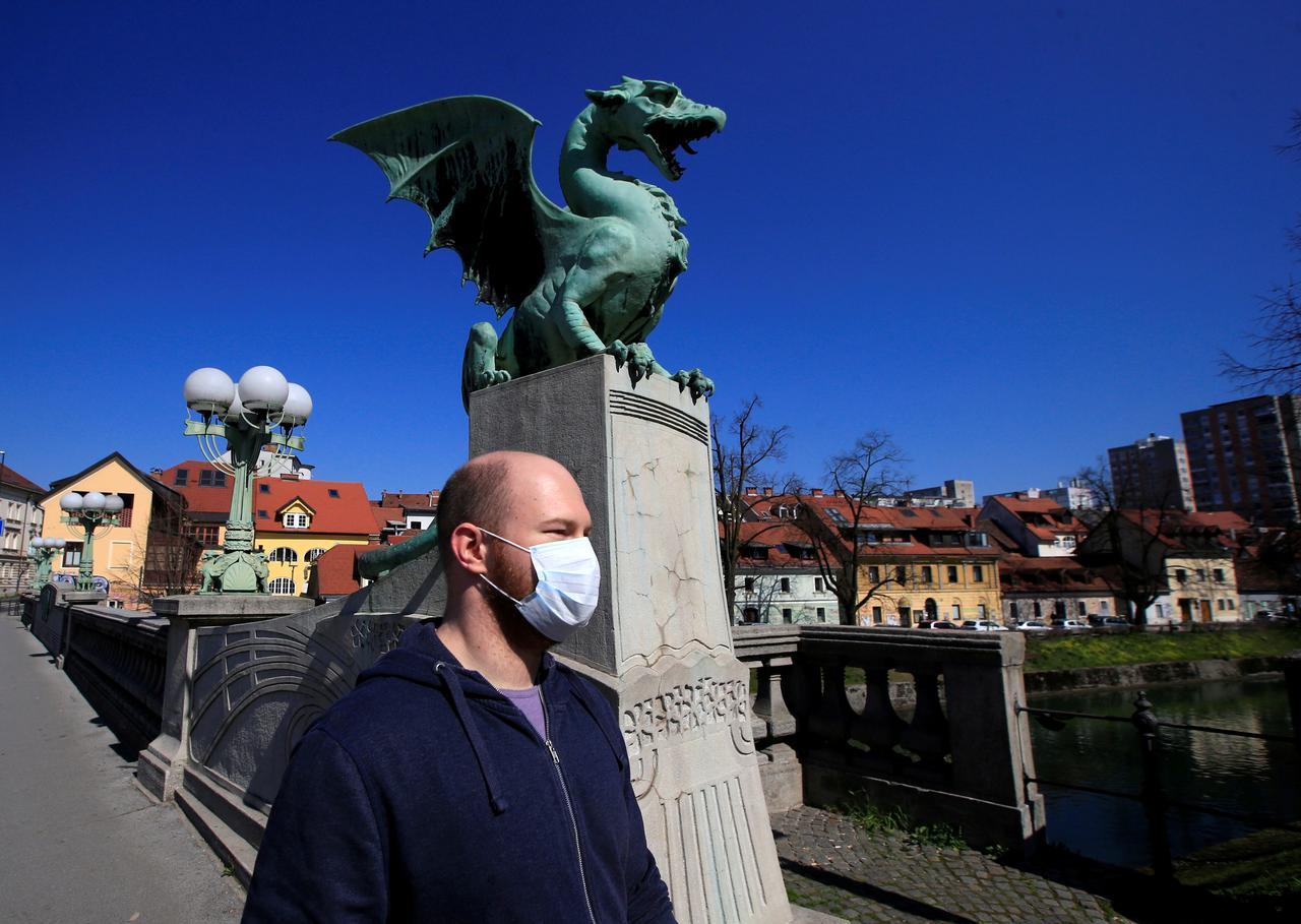 Ljubljana citizen with mask walks over the city's dragon bridge (Credit: Reuters)