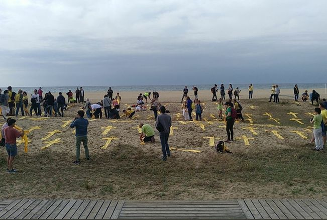 Yellow towels and scarves in form of cross on Mataró beach