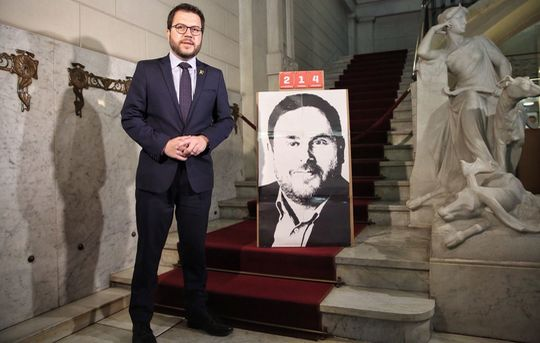 New Catalan vice-president Pere Aragonès standing beside portrait of his predecessor,Oriol Junqueras