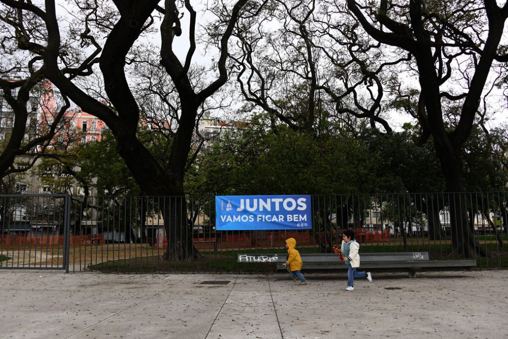 """Two children run past a banner that says, """"Together, we'll be fine,"""" in Lisbon, April 2020"""