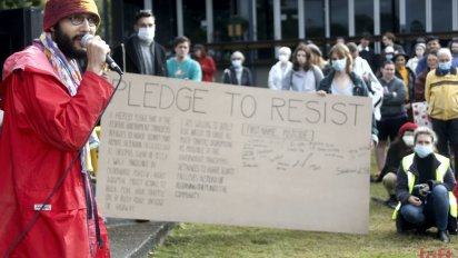 Greens coucillor Jonathan Sri encourages people to sign the pledge to resist