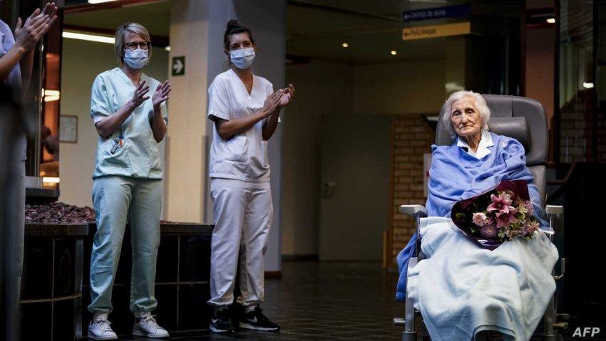 Belgian health workers salute 100-year-old COVID-19 survivor, Julia Dewilde as she leaves the Bois de l'Abbaye hospital (Credit: AFP)