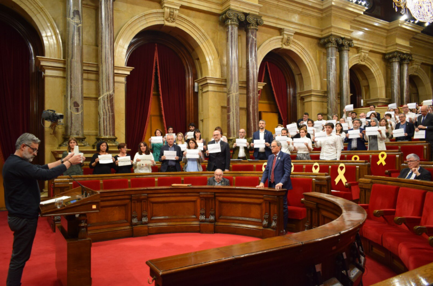Catalan pro-sovereignty MPs (the parliamentary majority) show posters reading #freeAssange in Thursday's session. The motion of support was moved by CUP spokeperson Carles Riera (at the lectern)