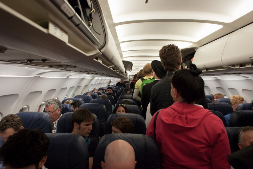 Passengers in a commercial aeroplane cabin.