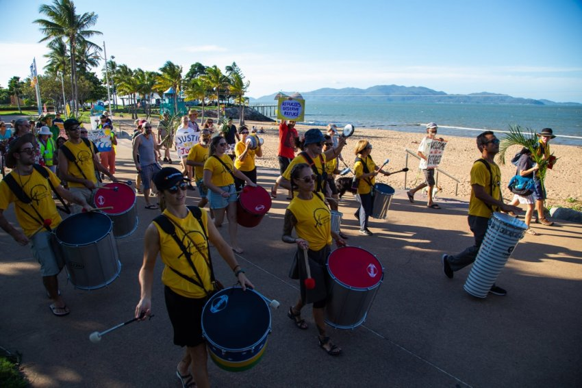 Townsville Drum Collective in full flight with Magnetic Island in the background. Photo: Amnesty Int