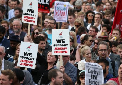 Protesters hold up a placards in support of Leader of the opposition Labour Party Jeremy Corbyn outside parliament during a pro-Corbyn demonstration in London in June last year.