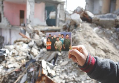 The hand of Yassir Mahmoud El Haj holding a picture of his family in front of the home in which Isra